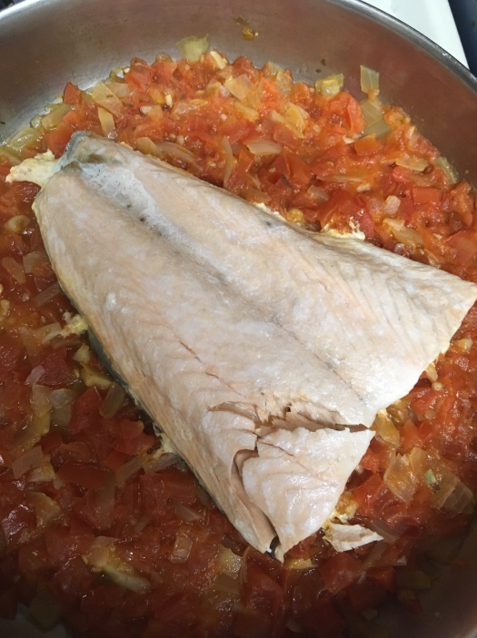 Using a bed of chopped tomatoes and onions keeps fish moist while it cooks. Photo by Laura Groch